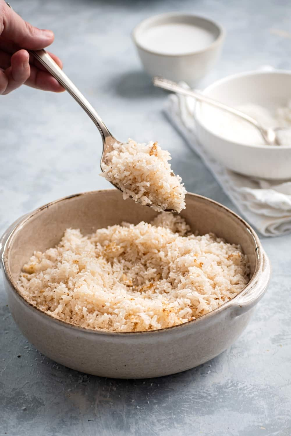 A bowl filled with coconut rice. A hand is holding a spoon over the ball with a scoop of coconut rice on it.