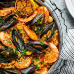 Part of a pan with seafood paella in it.