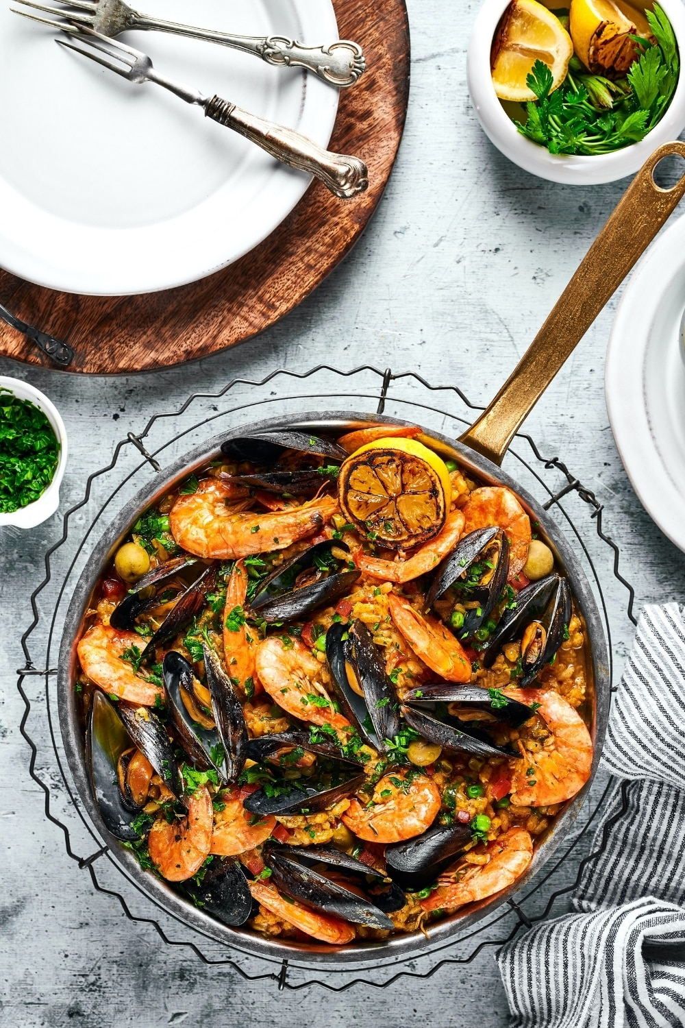 A pan with seafood paella in it. Behind it is part of a wooden serving board with a white plate on top with a fork on it. Everything is on a gray counter.