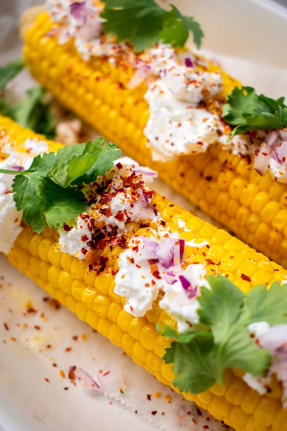 Two pieces of corn on the cob with a Mexican queso fresco mixture and cilantro leaves on top.