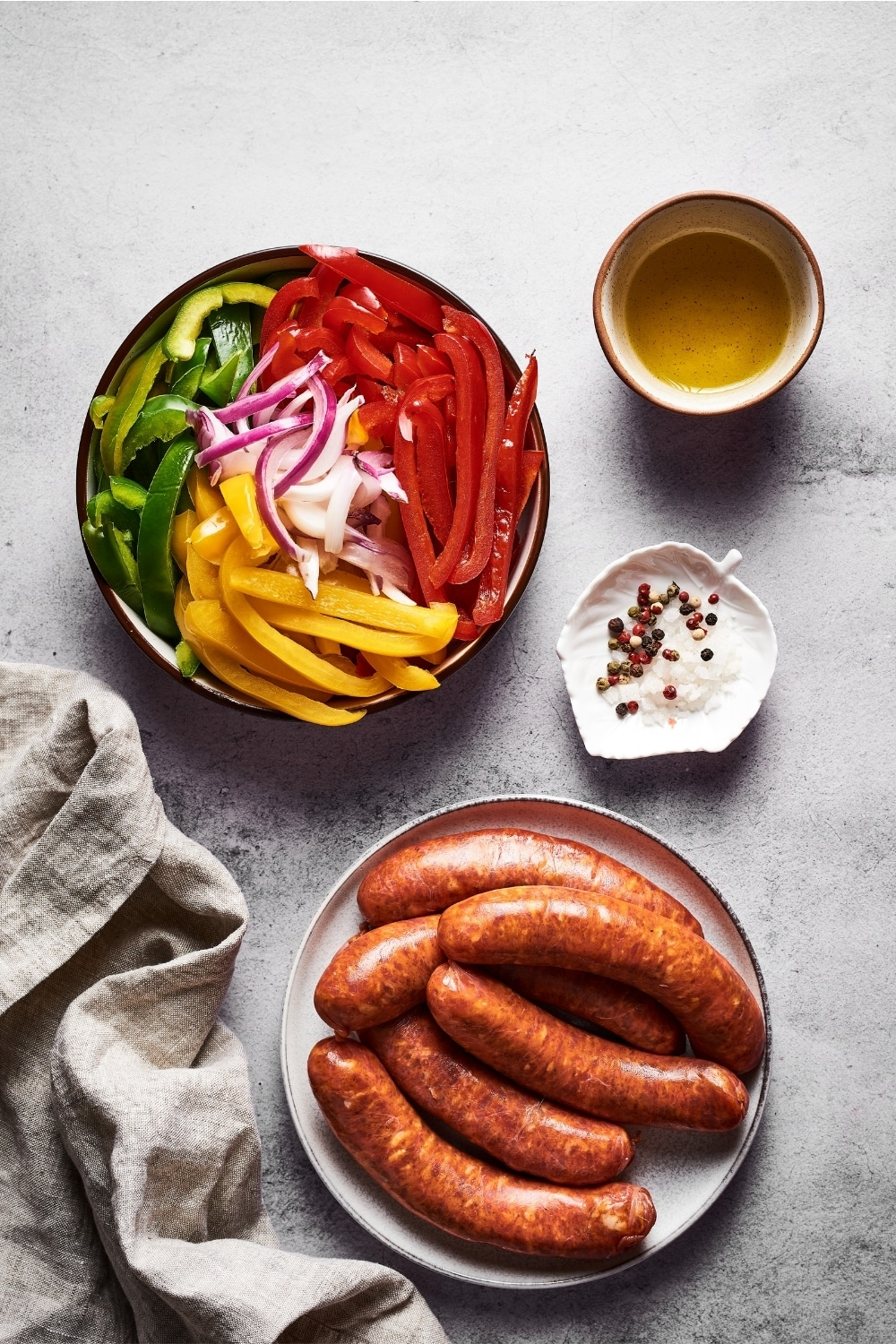 A white plate with Italian sausage on it. Behind that is a bowl with sliced red, yellow, and green peppers and onions. Next to the ball is a small white bowl with olive oil in it and in front of that is a small white leaf bowl with salt and pepper.