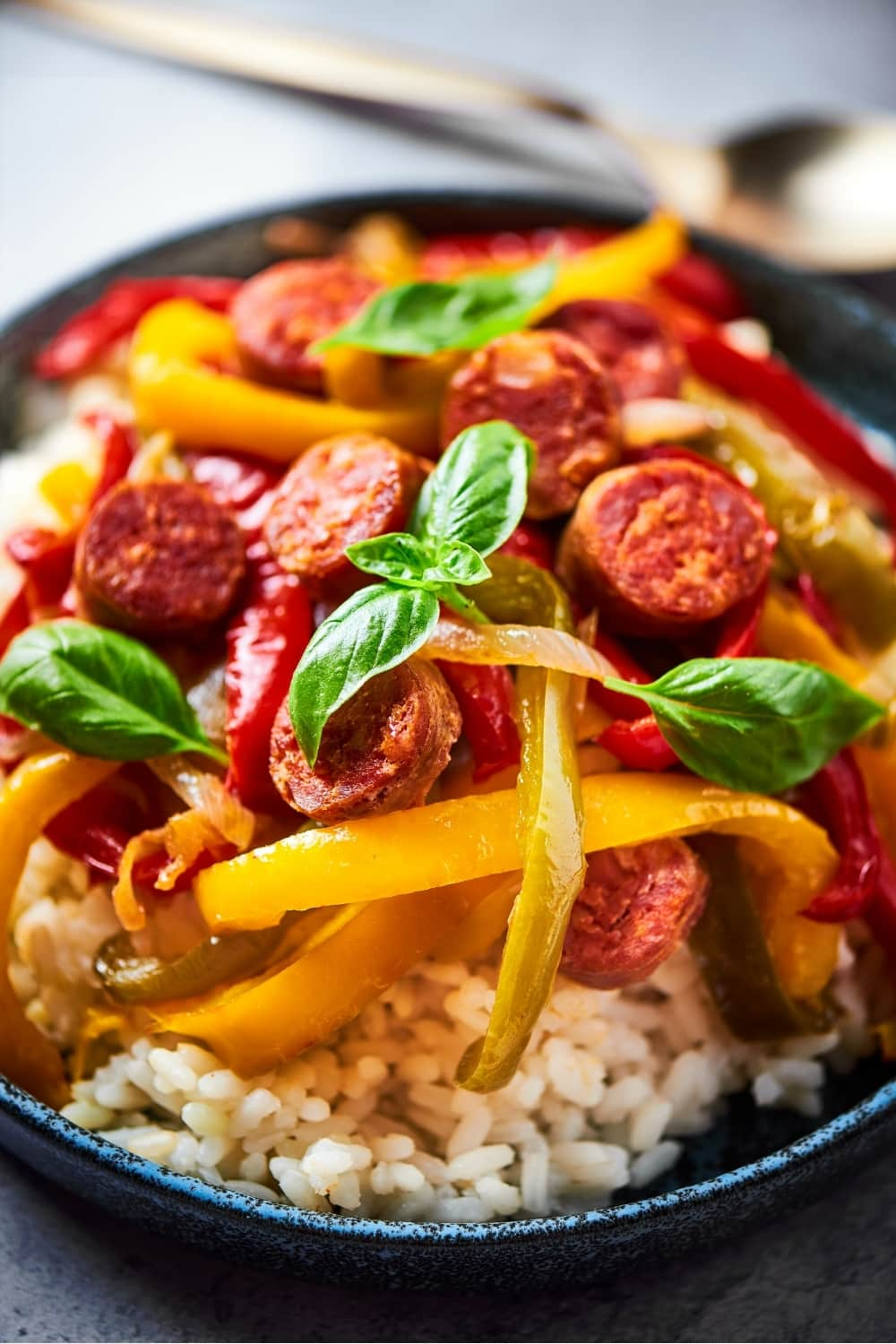 A bowl filled with white rice, sliced red, green, yellow peppers and onions, and slices of Italian sausage.