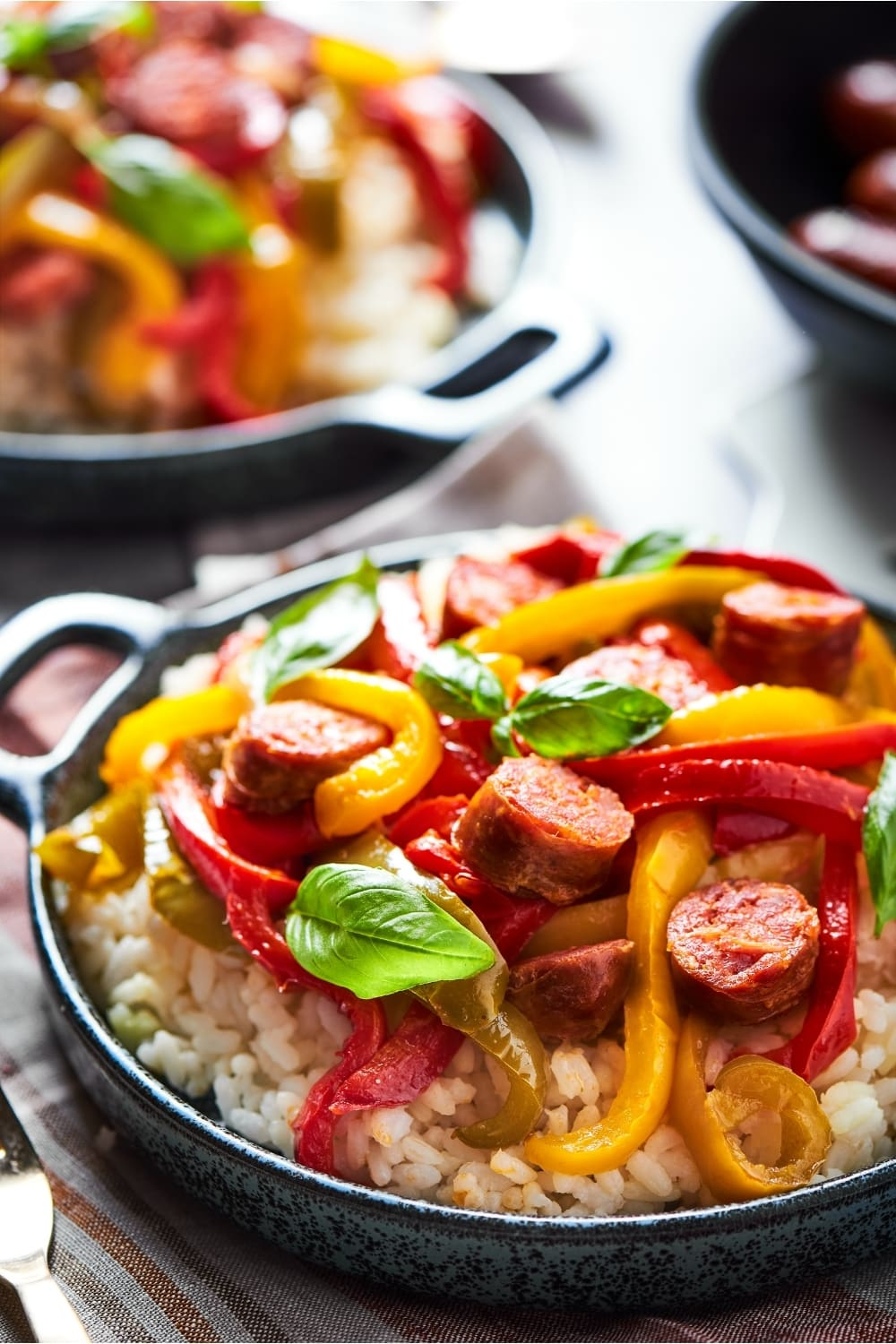 A bowl filled with white rice with sliced red, green, and yellow peppers and onions and slices of Italian sausage on it.