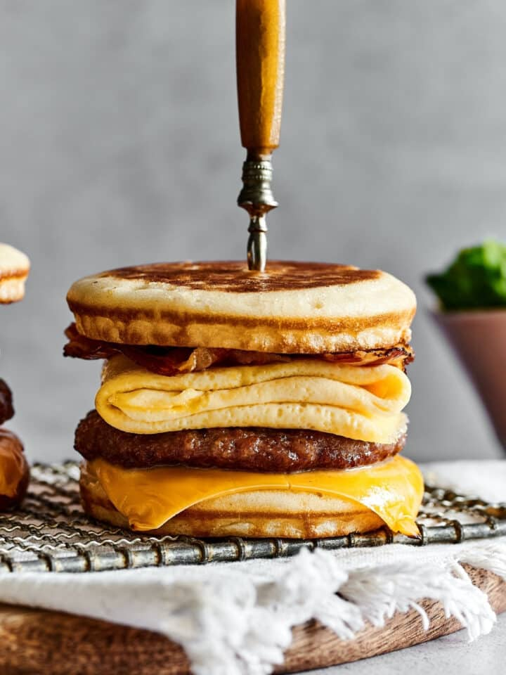 A sausage, meat, and cheese McGriddle on a wire rack on a white tablecloth on a wooden board on top of a counter. There is a knife through the top center of the McGriddle.