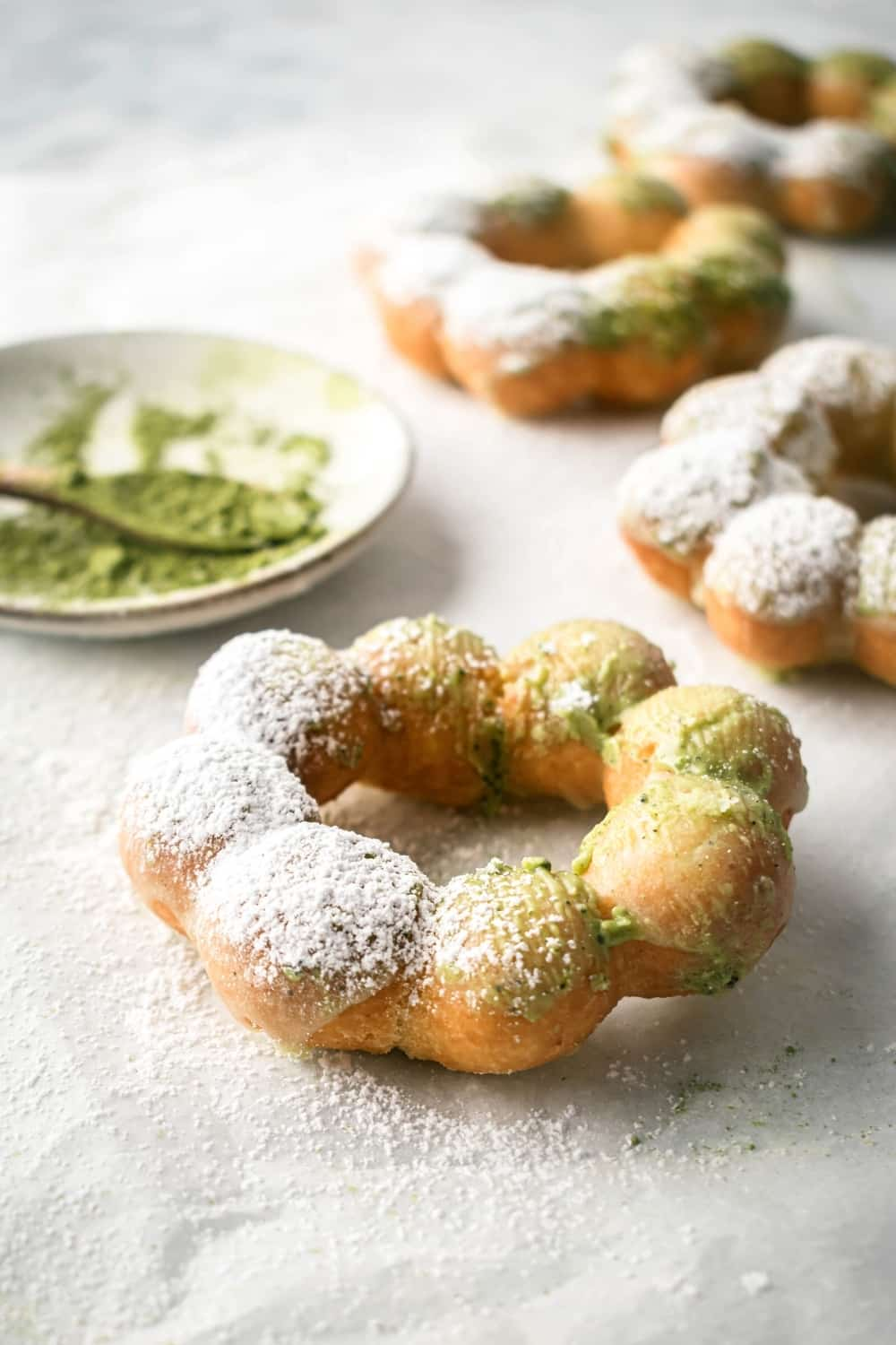 A mochi donut a piece of parchment paper. There are three mochi donuts behind it and a small plate with matcha powder on it.