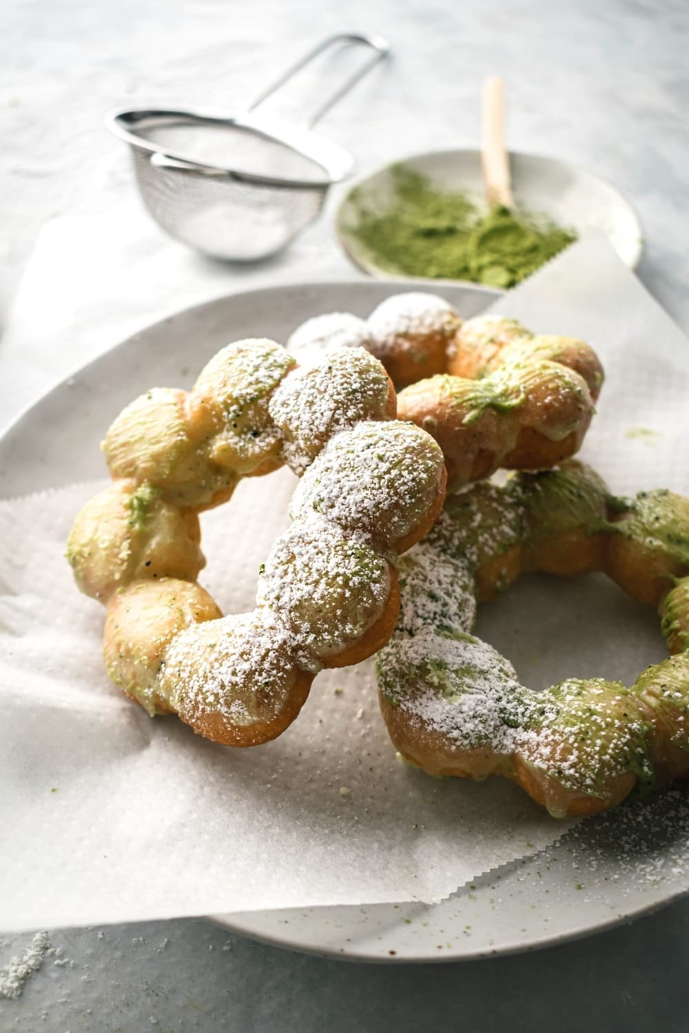 Three mochi donuts overlapping one another on a paper towel on top of a white plate. Behind it is a mesh sieve with powdered sugar in it and a small plate with matcha powder on it.