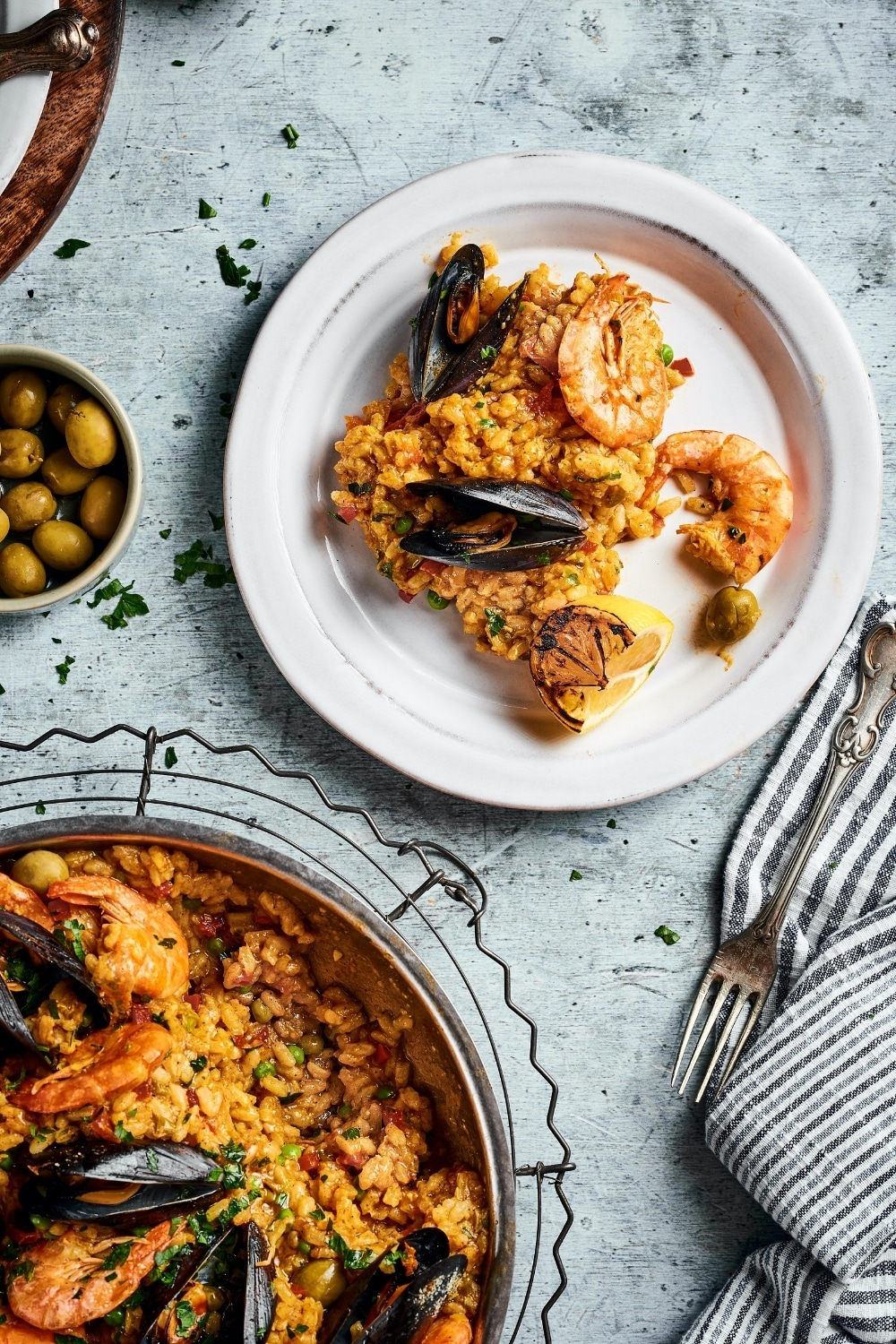 Part of a pan with seafood paella in it. A scoop from the part of the pan is on a white plate on a gray counter.