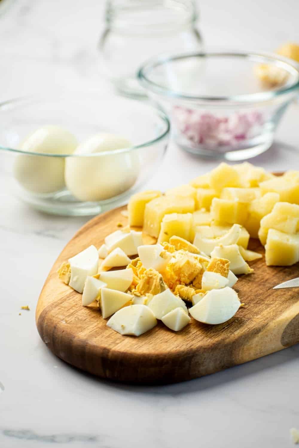 A woden cutting board sliced hard-boiled cubes of potatoes behind it. To the left of the cutting board is a glass bowl with two hard boiled eggs and next to that a glass bowl with chopped red onion.