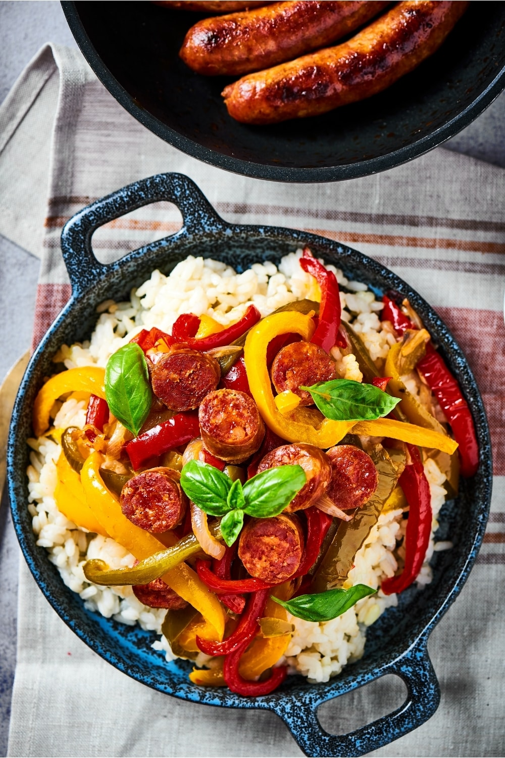 A bowl with sliced sausage, sliced red, yellow, and green peppers, and onions all on top of white rice. The ball is on a plaid tablecloth.
