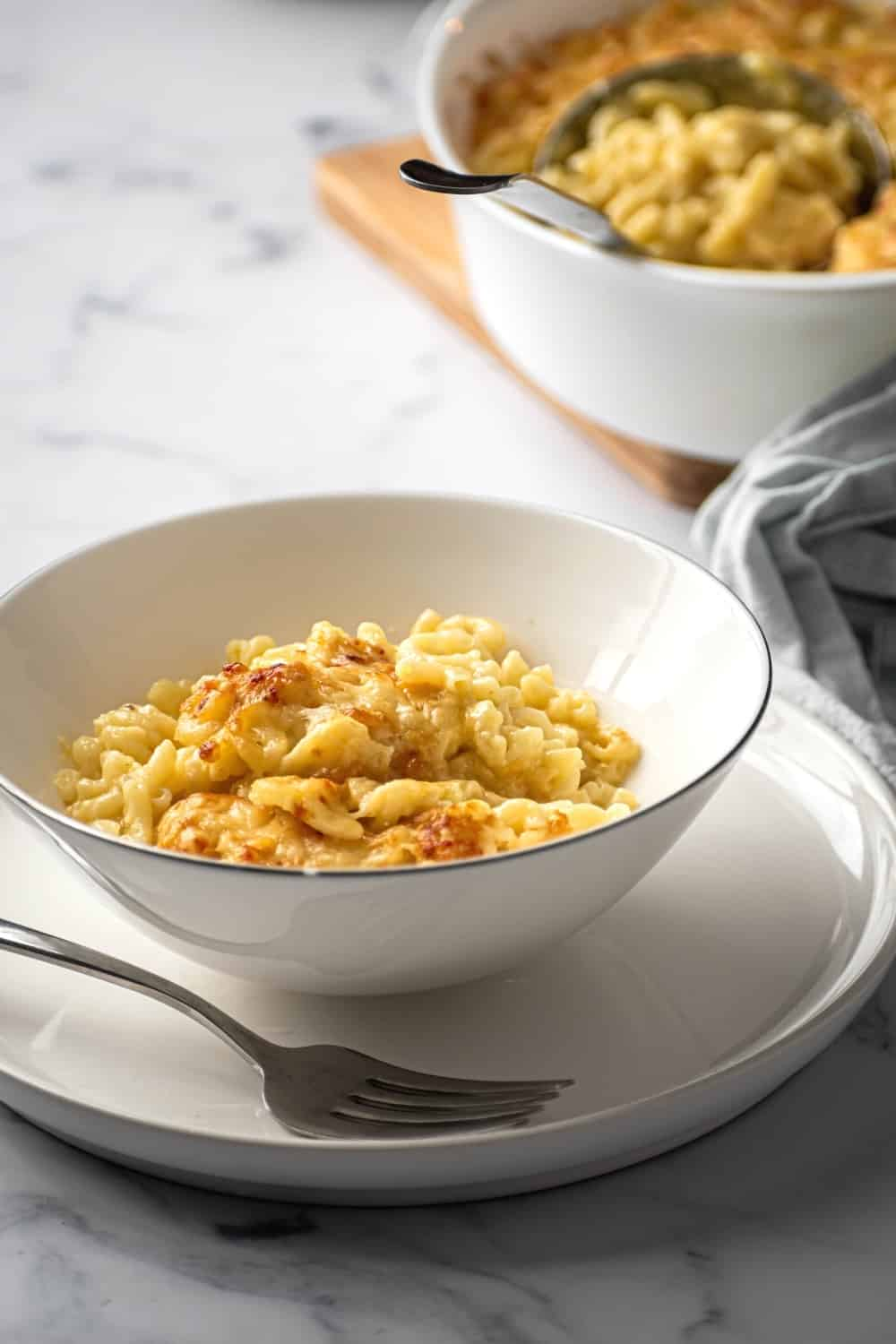 A white bowl with mac & cheese in it on a white plate. There is a fork on the plate and the plate is on a white counter. Behind it is part of a white dish with mac & cheese in it.