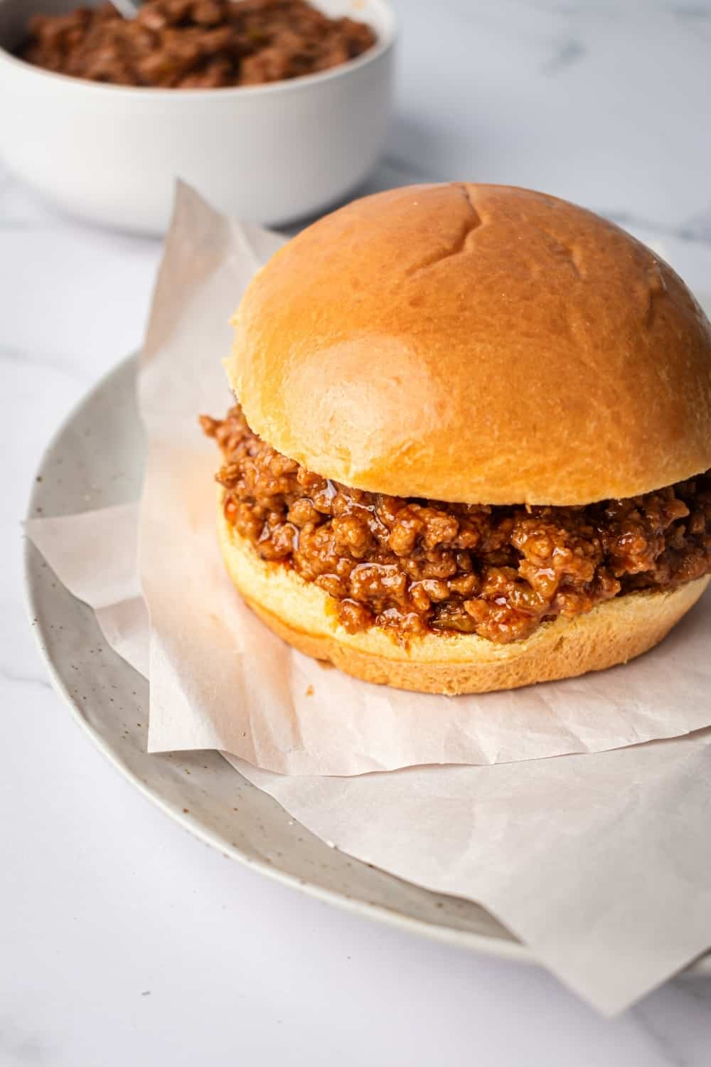 A sloppy Joe on two pieces of parchment paper spread across a gray plate. The plate is on the white counter and behind the plate is part of a white bowl filled the sloppy Joes.