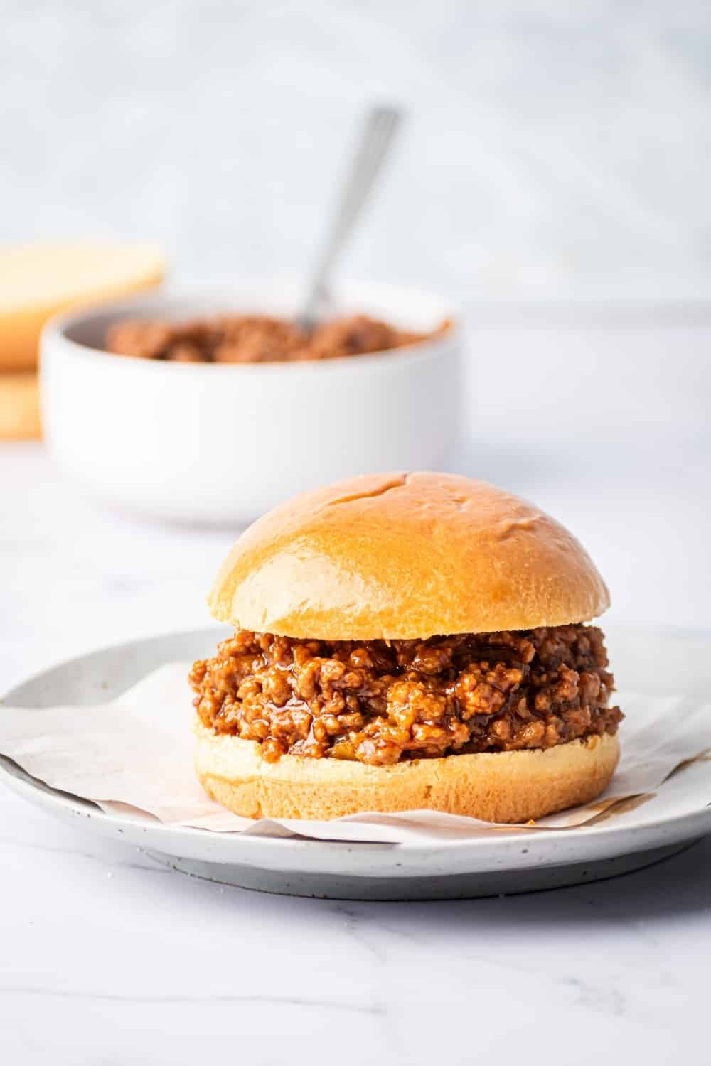 A sloppy Joe on a piece of parchment paper on a gray plate. The gray plate is on a white counter behind it is a white bowl filled with sloppy Joes.