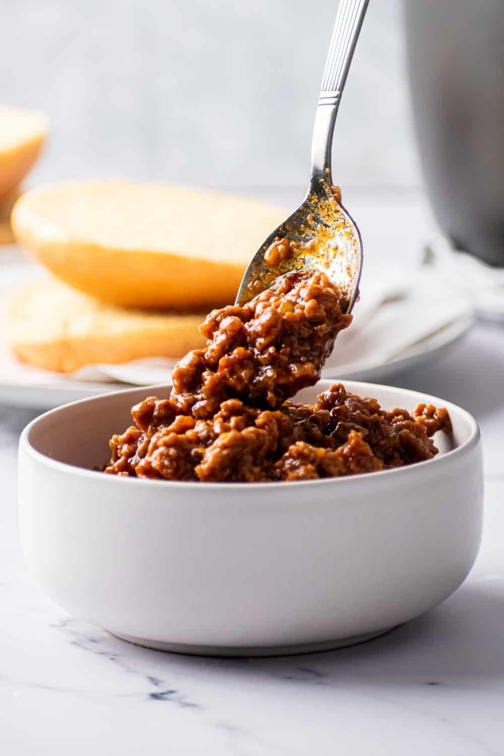 A white bowl on the white counter filled with sloppy Joes. There is a spoon hovering over the bowl spoon in some sloppy Joe into the bowl. Behind the bowl is a brioche bun on a piece of parchment paper on a gray plate.