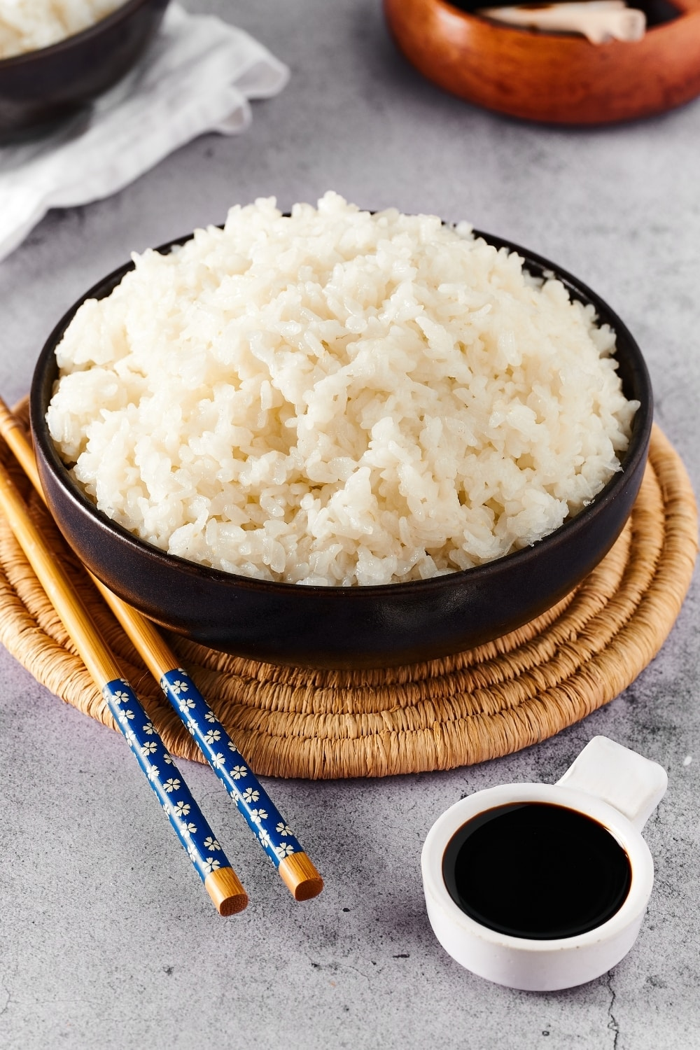 Instant pot sushi rice and a black bowl and a straw circular placemat. To the left of the bowl on the placemat is a pair of chopsticks and in front of the placemat as a small white bowl filled with soy sauce.