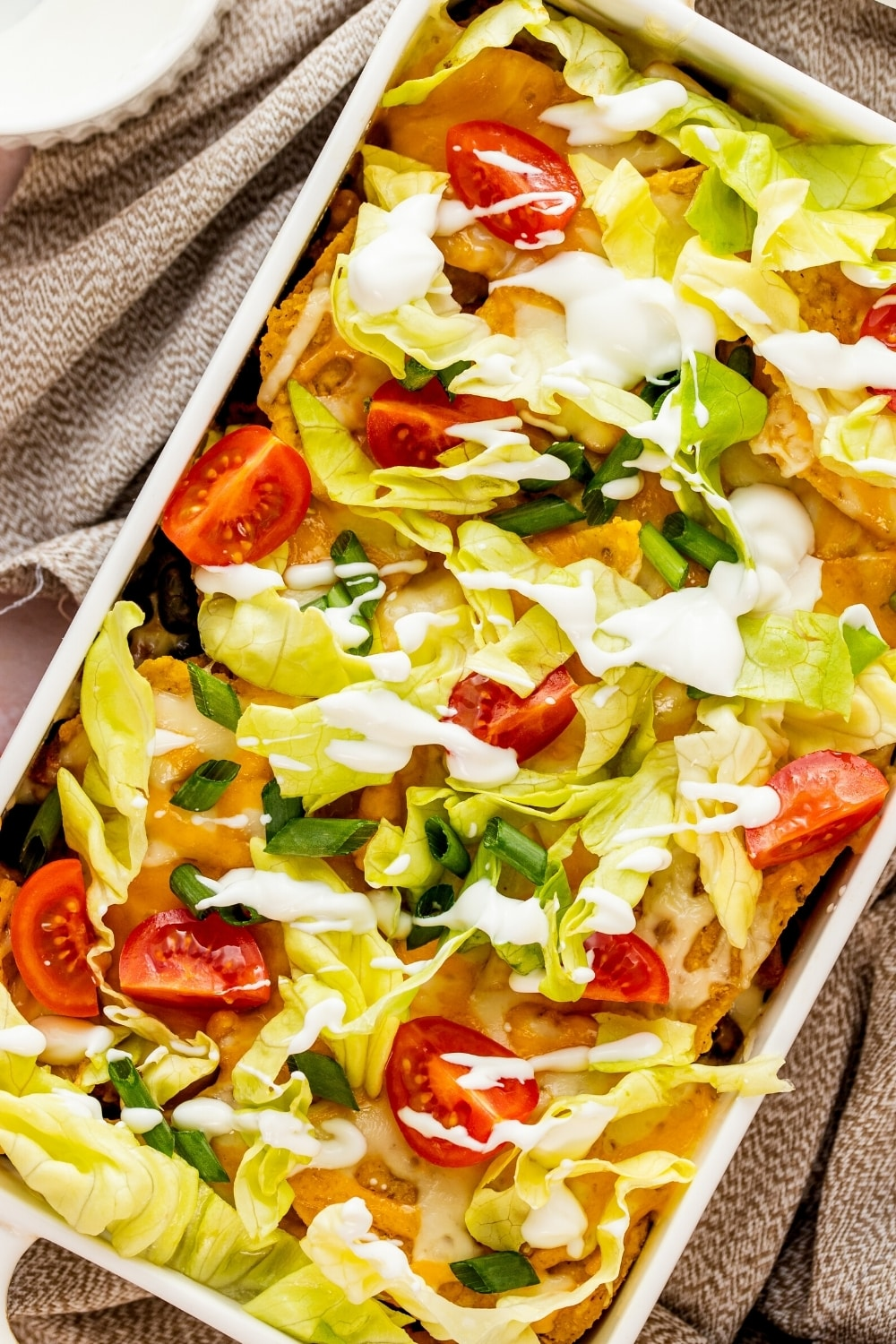 A white casserole dish filled with walking taco casserole.