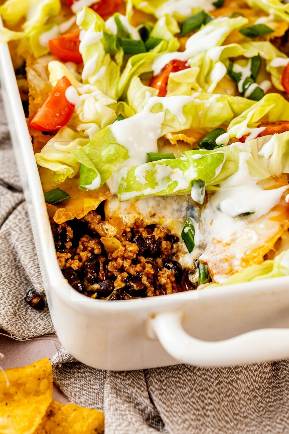 Part of a white casserole dish with walking taco casserole in it. The front corner of the casserole dish is showing the inside of the walking taco casserole.