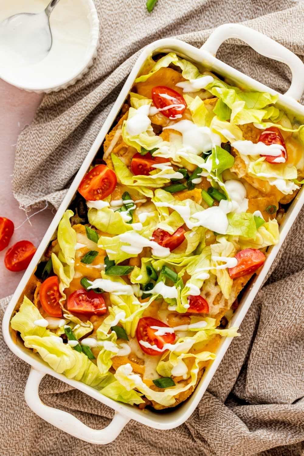 White casserole dish with walking taco casserole in it. The casserole dish is on a gray tablecloth and there is part of a small white bowl of sour cream behind it.