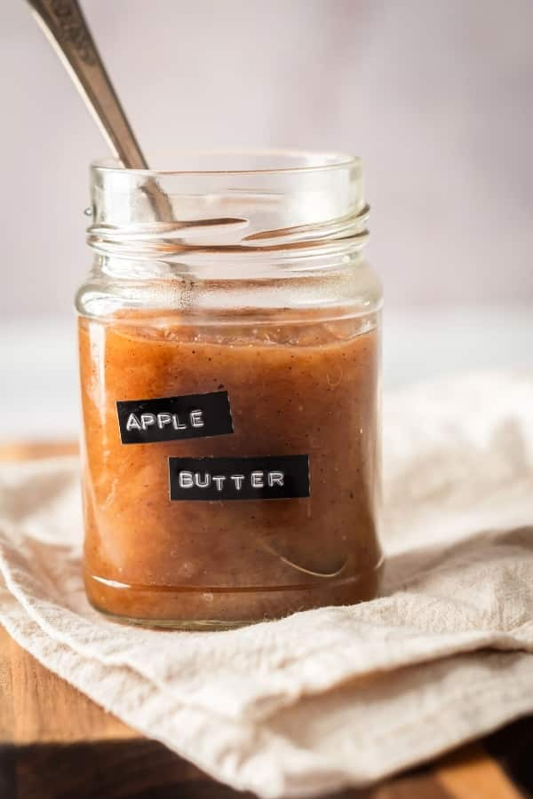 A glass jar that is filled with apple butter on top of a white tablecloth on a wooden board. The jar has an apple butter label on it and there is a spoon submerged in the apple butter in the jar.
