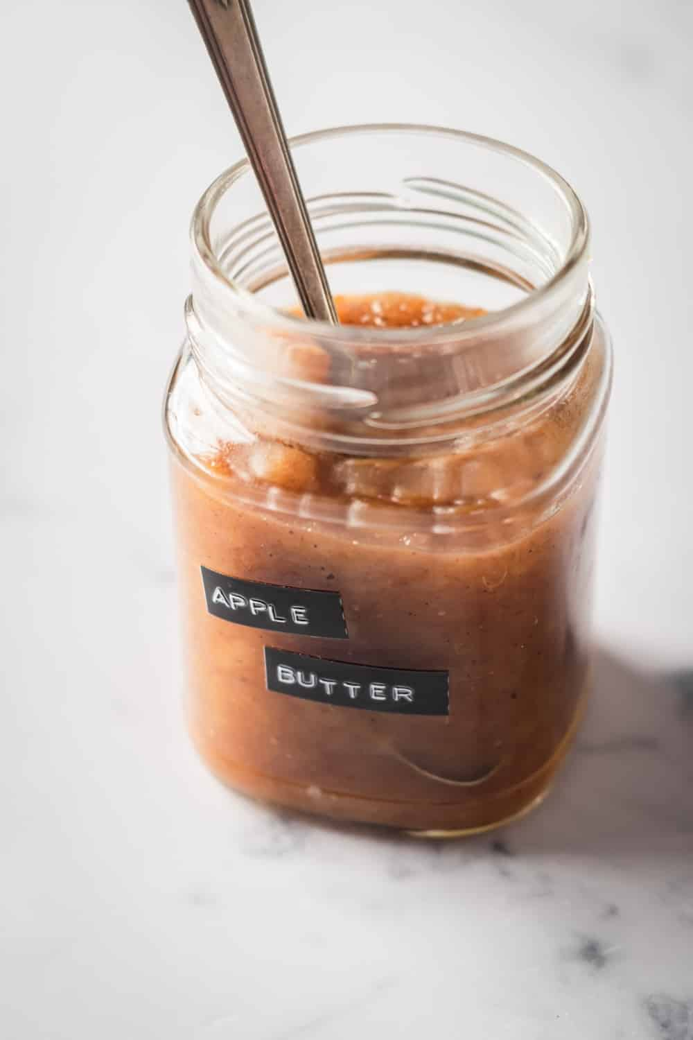 A glass jar filled with apple butter with a spoon in it. The jar has apple butter labeled on it.