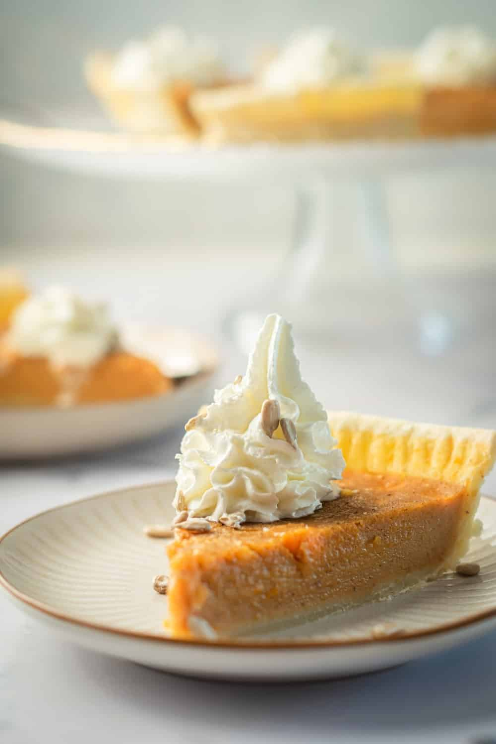 A slice of pumpkin custard pie on a white plate on a white counter.