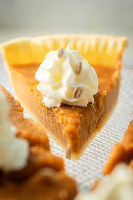 A slice of pumpkin custard pie on a glass pie tray.
