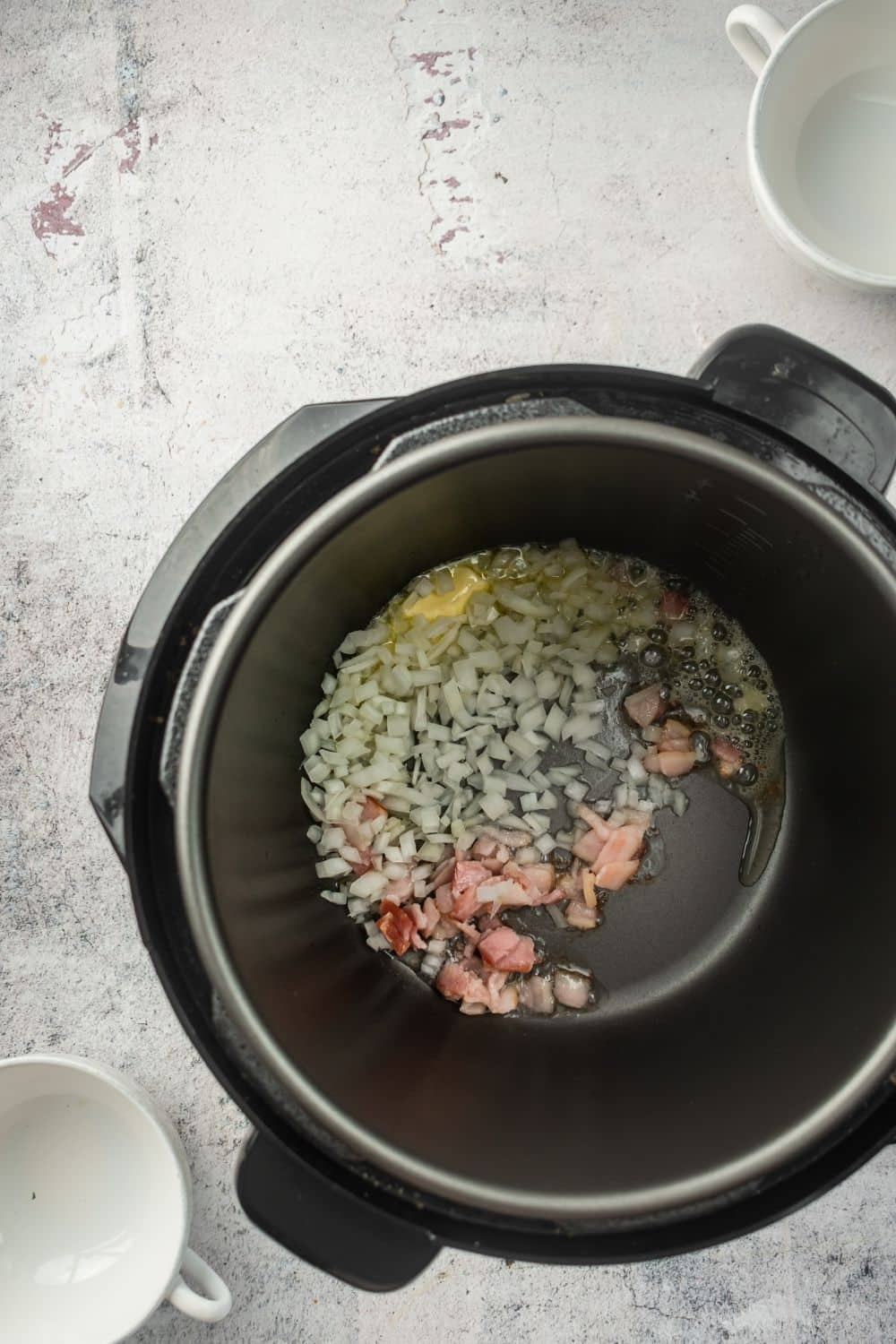An instant pot on a white counter filled with onion and bacon bits in it.