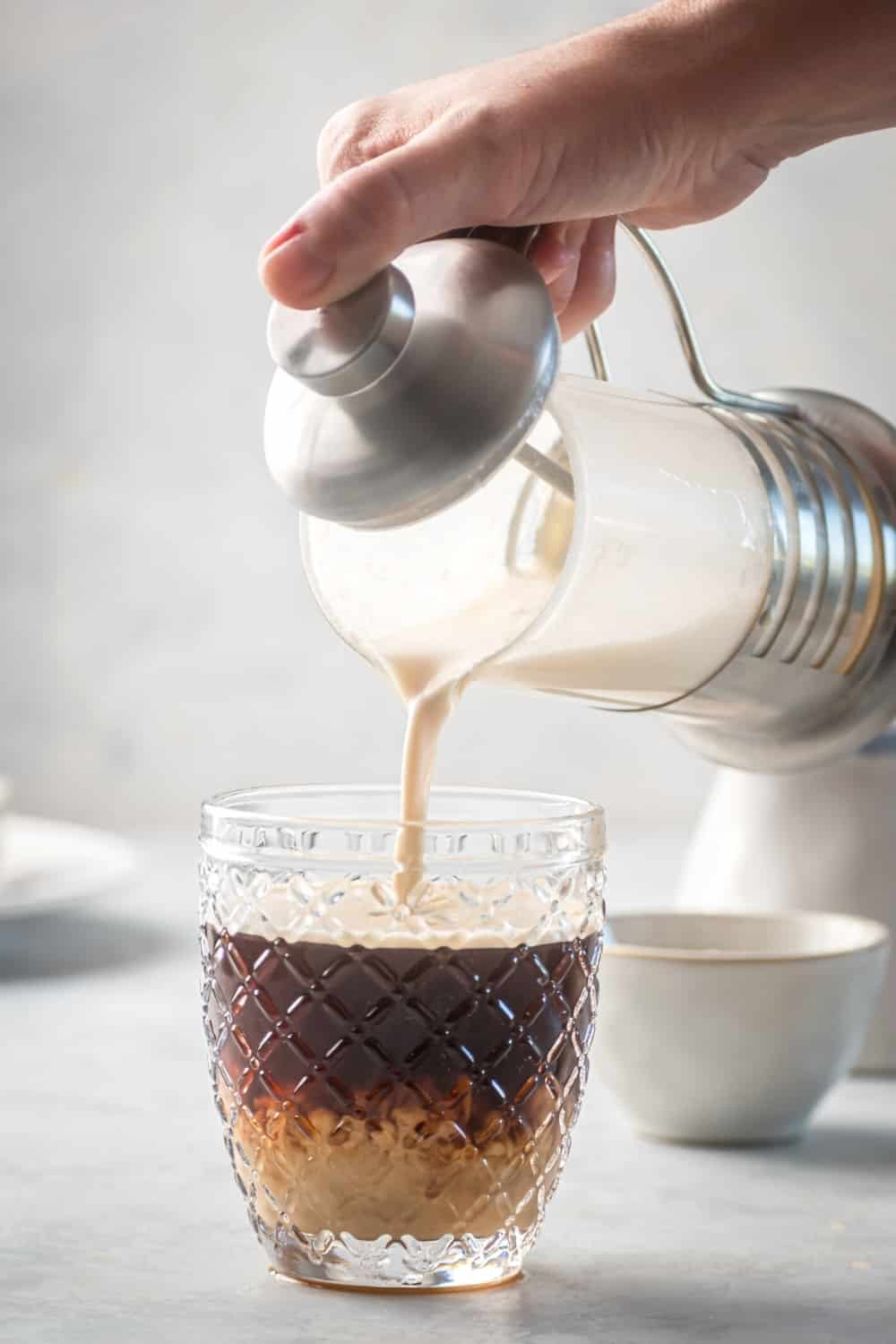 A glass cup of espresso and a gray counter. The hand is pouring sweet cream cold foam from the French press into the cup.