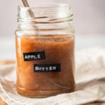 A glass jar that is filled with apple butter with a spoon in it on top of a white table cloth. There's a spoon submerged in the jar of apple butter.