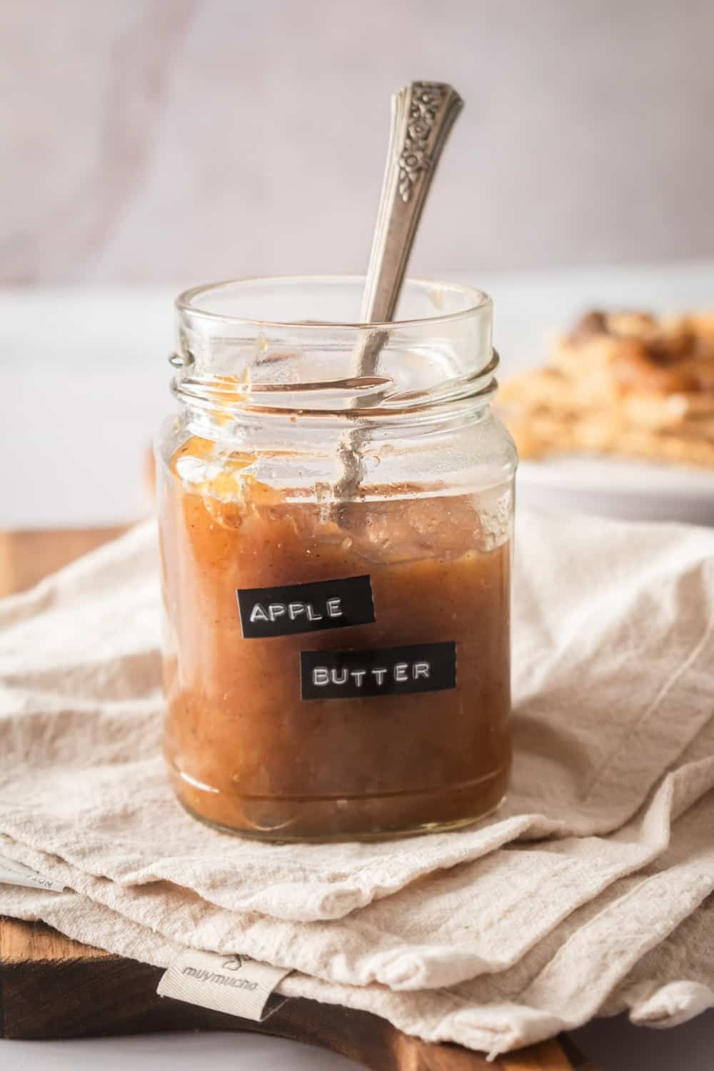 A glass jar filled with apple butter on top of the tablecloth on the wooden board. There's a spoons in the apple butter and apple butter is written on a black label on the jar.