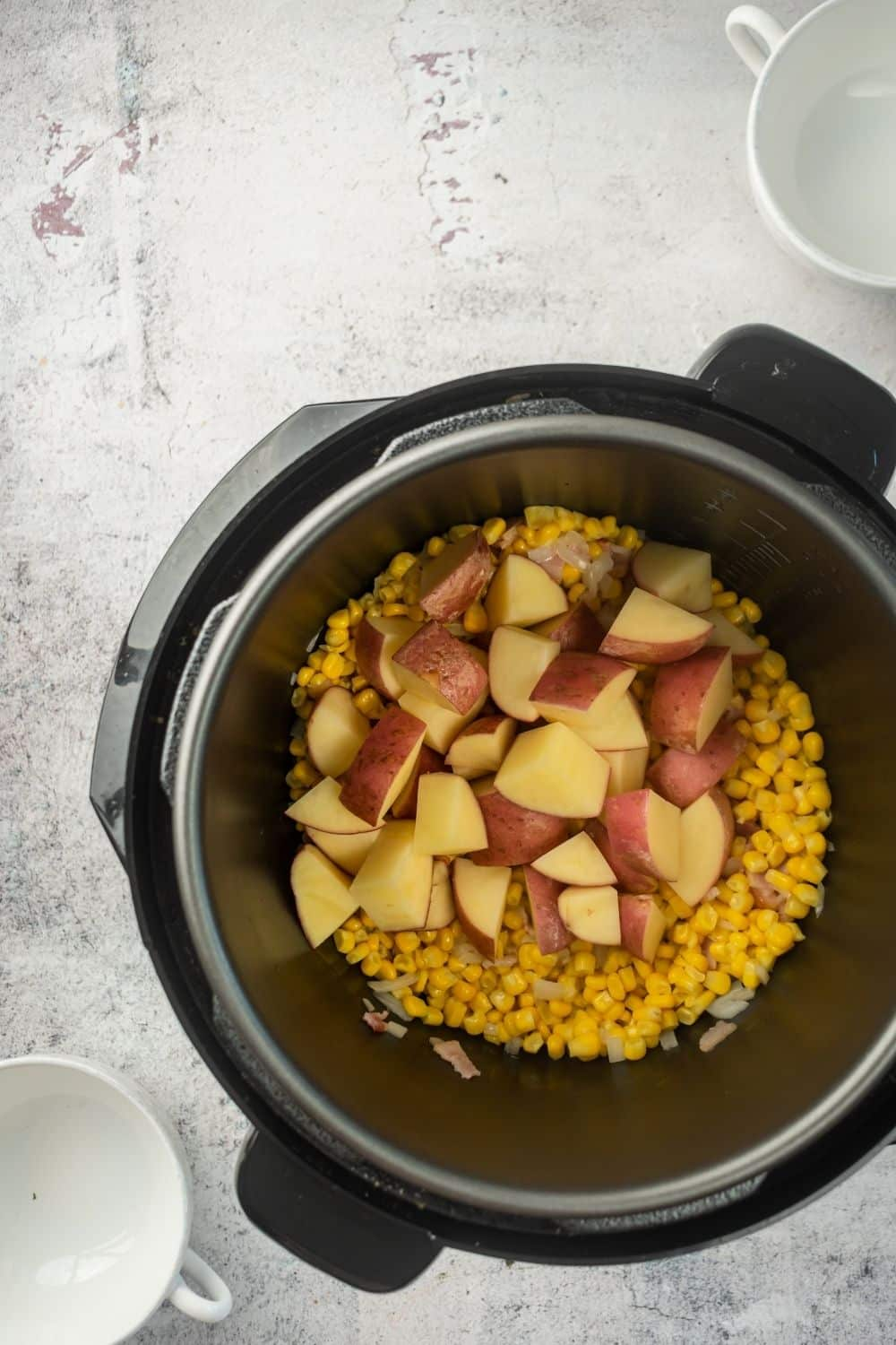 An instant pot on a white counter filled with corn and red potato pieces in it.