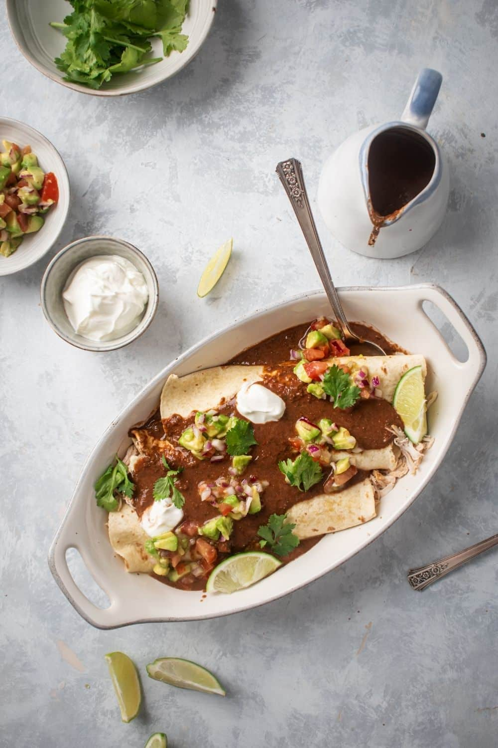 An oval white dish on a gray counter filled the chicken enchiladas. There are a few lime wedges around it and behind it's a small whiteboard sour cream and a pitcher of enchilada sauce.