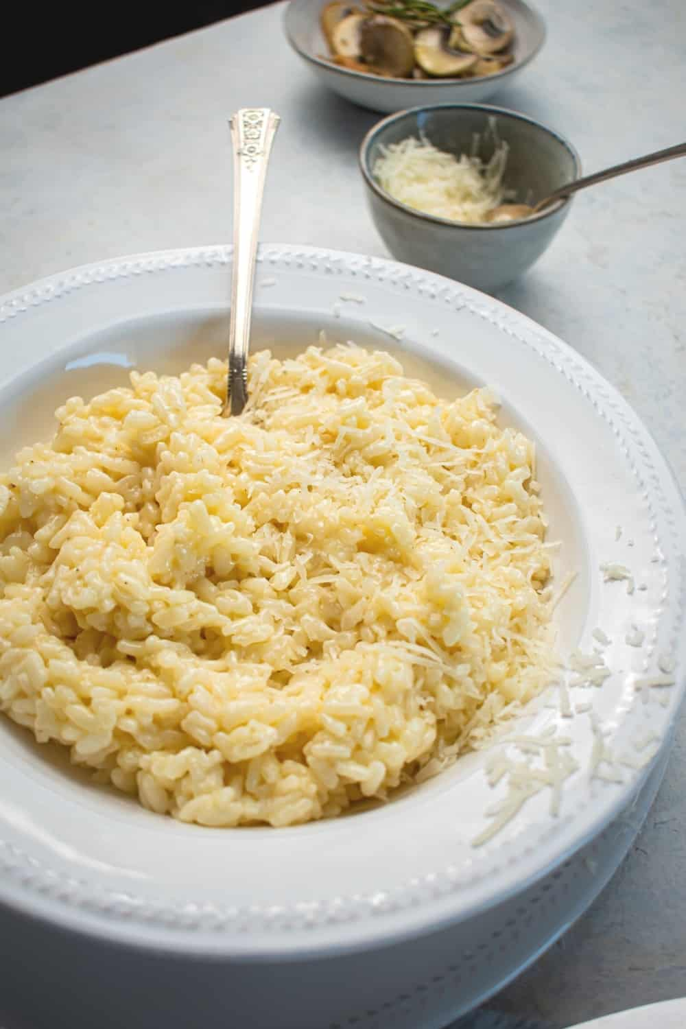 Part of a white plate with part of a white bowl on it filled with risotto with a spoon submerged in it. Behind a bowl of risotto is a small bowl of Parmesan cheese and part of a bowl of mushrooms.