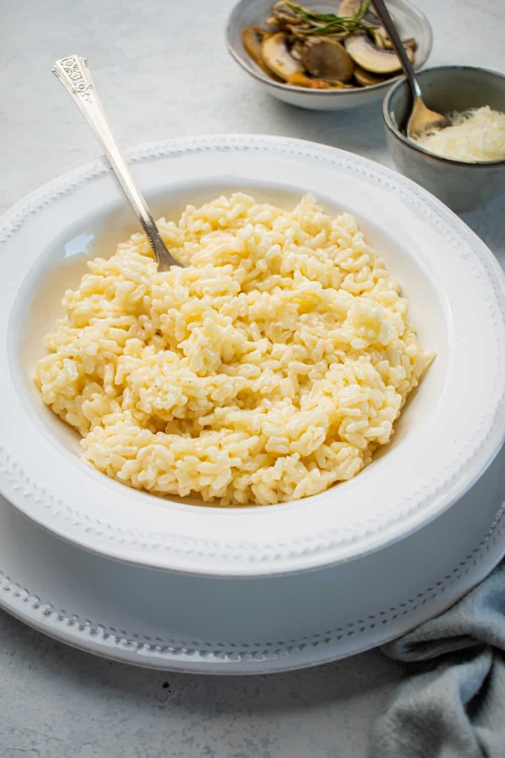 A gray counter with a white plate on it with a white bowl filled with risotto. There was a spoon in the risotto and behind the ball is a small bowl of Parmesan cheese and a small bowl of mushrooms.