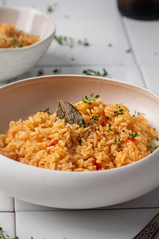 Spanish rice in a white bowl on white tile.