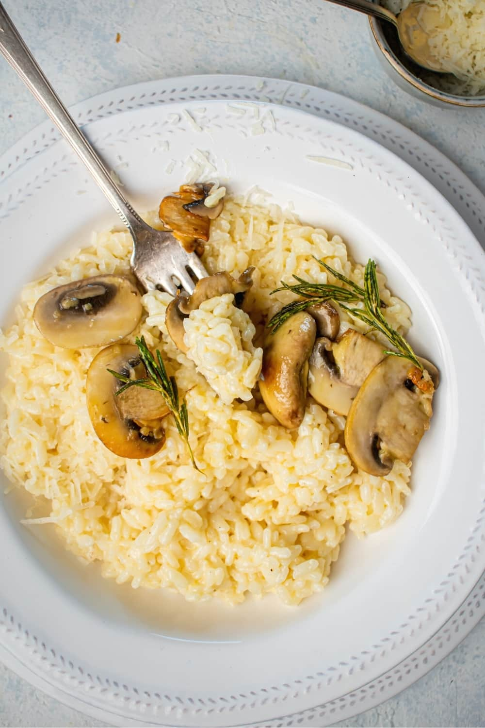 White bowl filled with mushrooms Odo with a fork sticking a piece of mushroom and some risotto in it.