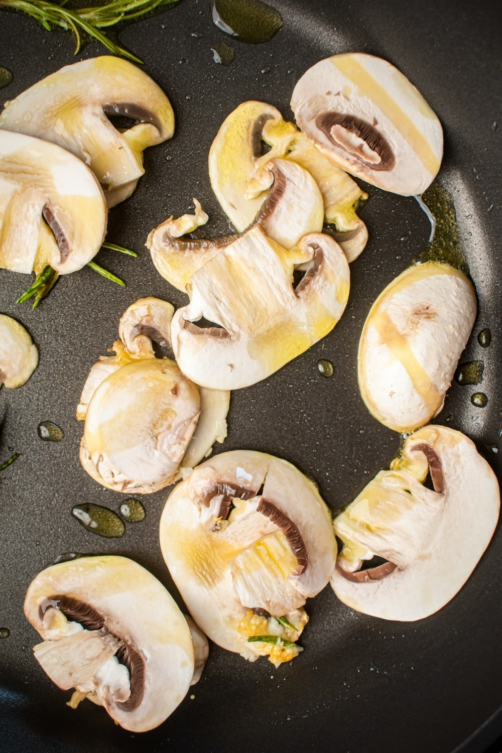Mushrooms drizzled with olive oil in a skillet.