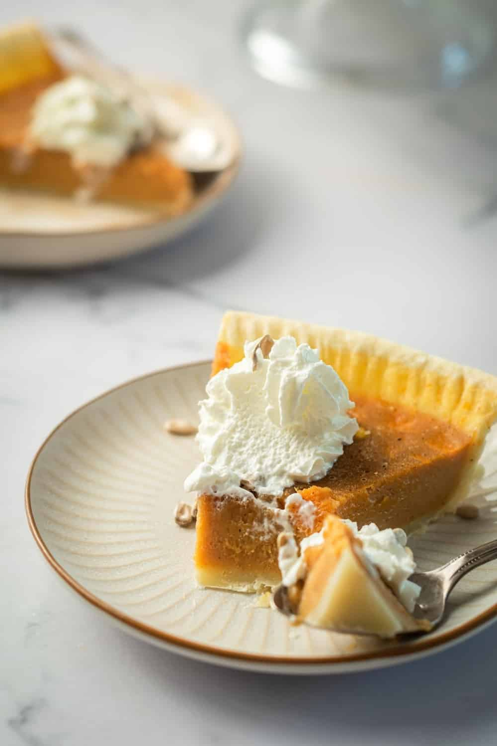 A slice of pumpkin custard pie on a white plate. In front of it on the plate is a spoon with the front piece of the pumpkin pie on it.