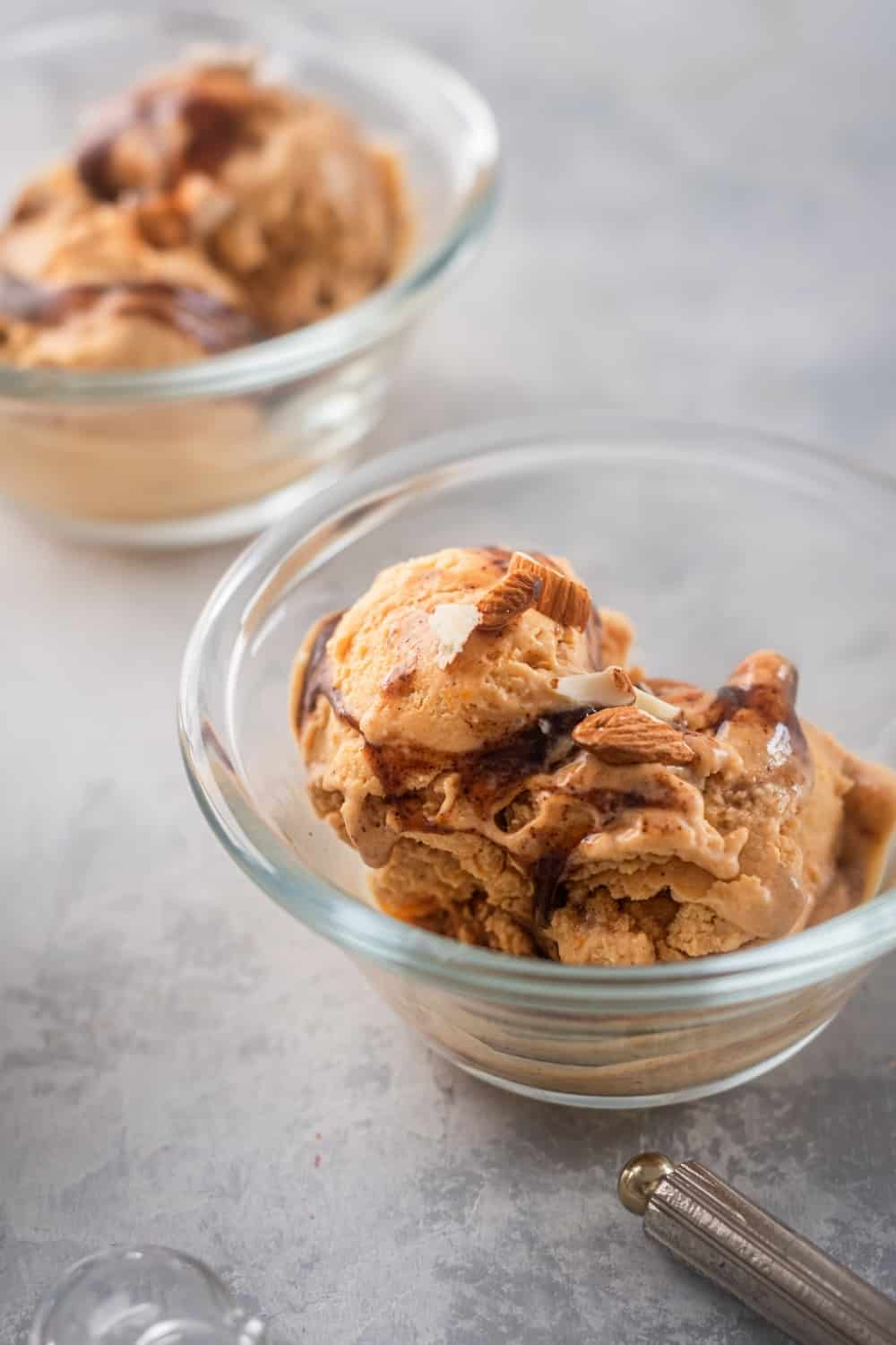 A glass on a grey counter bowl filled with two scoops of pumpkin ice cream. Behind it is part of another glass bowl filled with pumpkin ice cream.