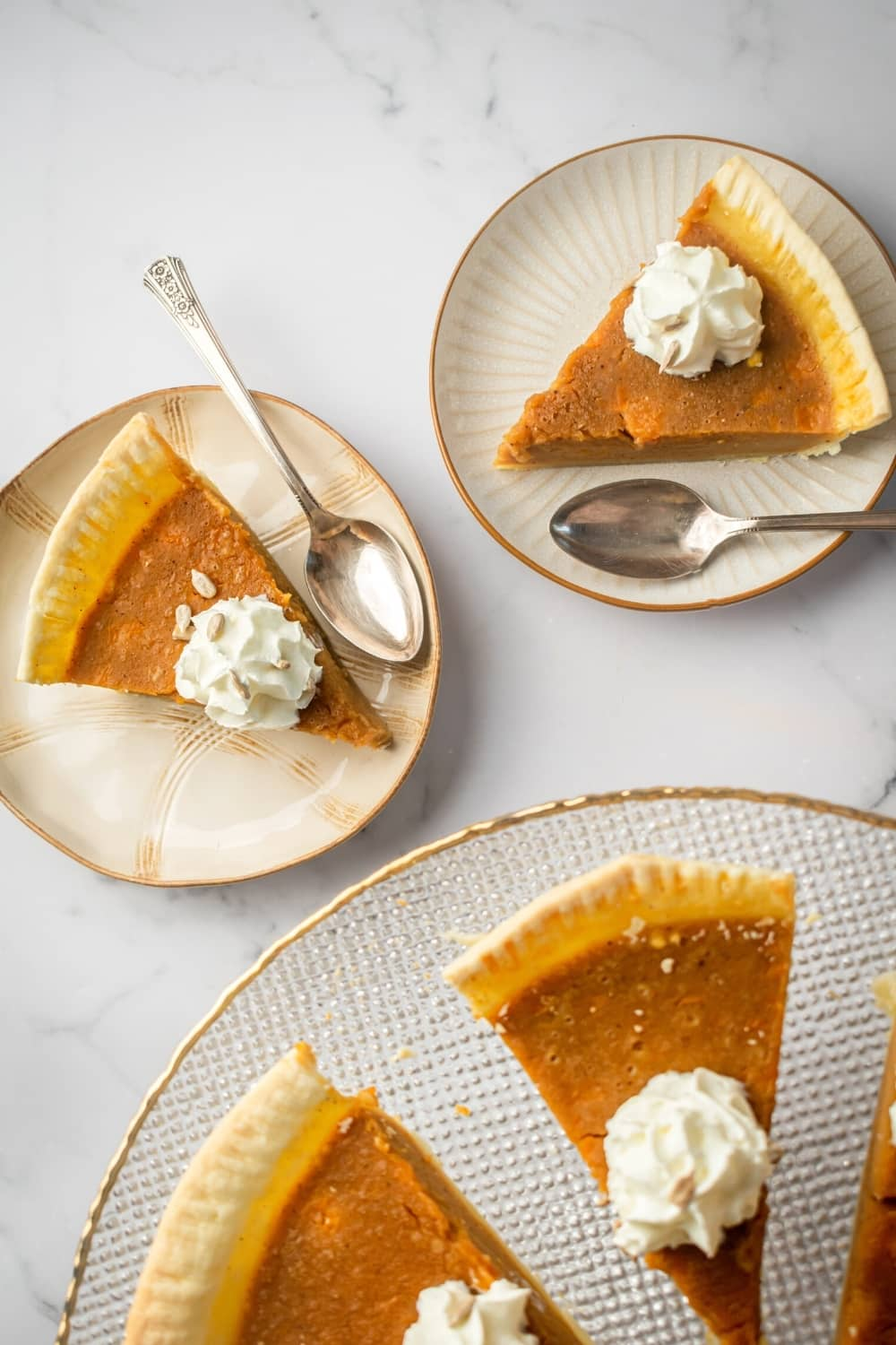 Two white plates with a slice of pumpkin custard pie on each. There are spoons on the plates and in front of them is part of two slices of pumpkin custard pie on a glass serving dish.