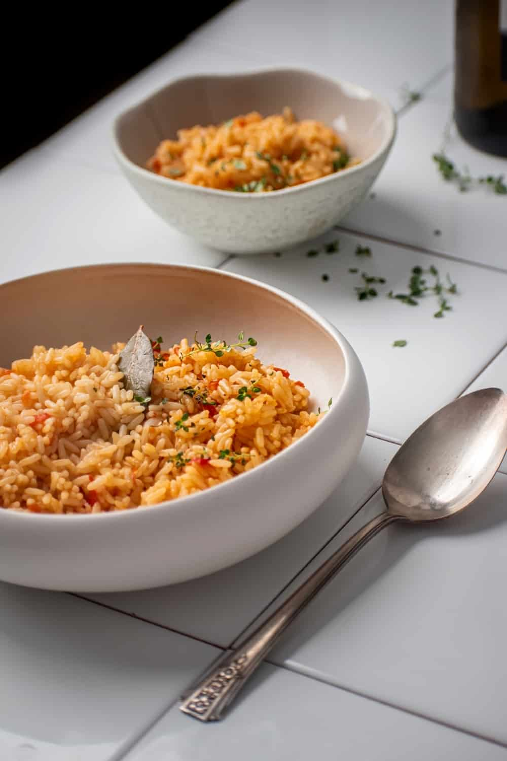 Part of a white bowl filled with Spanish rice on white tile. There is a Silver spoon next to the bowl in behind the ball is a smaller white bowl filled with Spanish rice.
