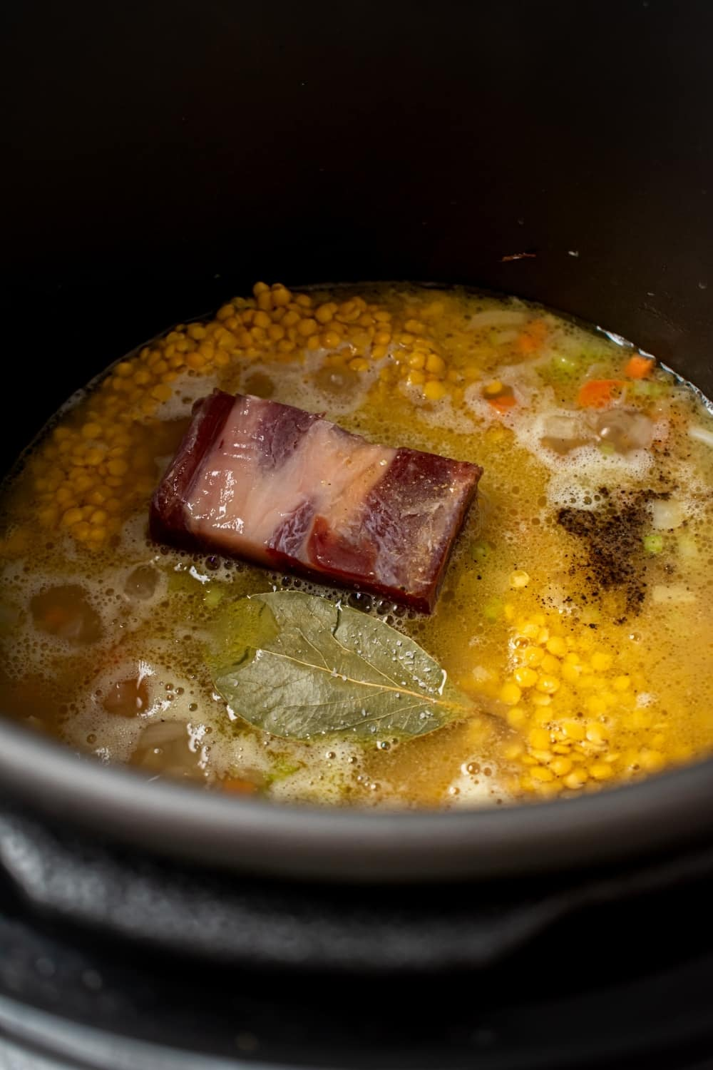 An instant pot filled with all of the ingredients for split pea soup.