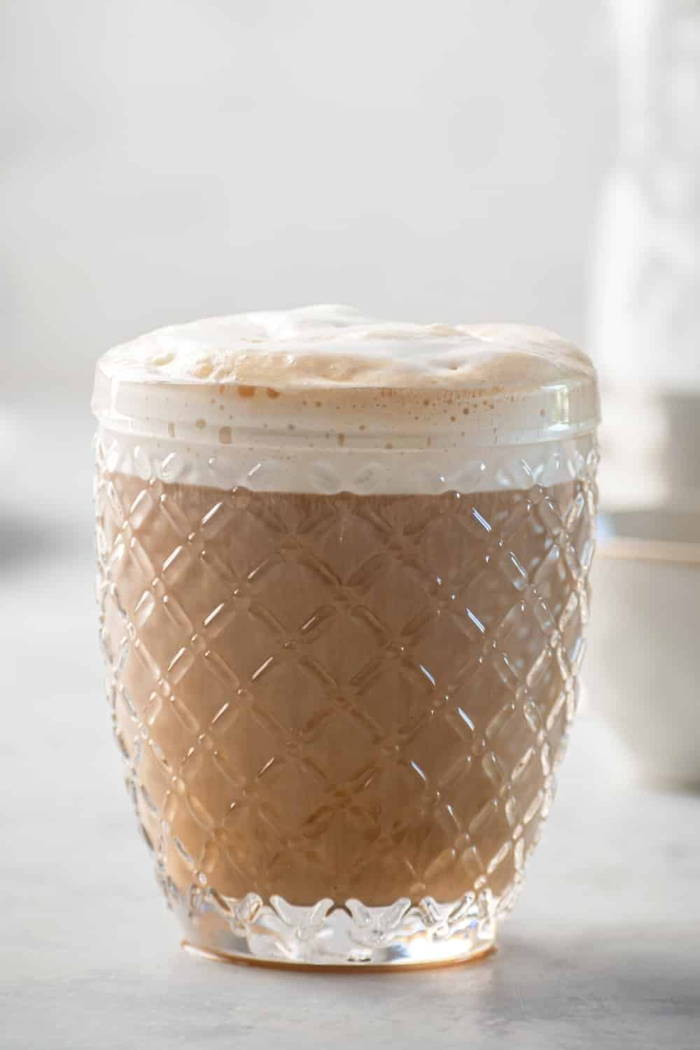 A glass of iced coffee with sweet cream cold foam on top and a gray counter.