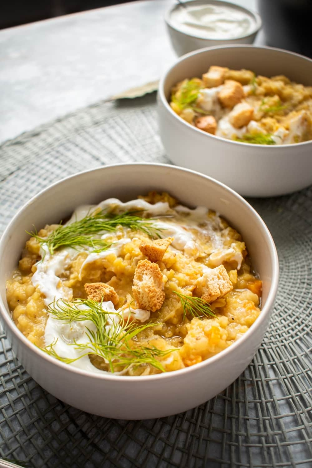 A white bowl filled with split pea soup and a gray placement. Behind it is another whiteboard that is filled with split pea soup and behind that is a small white bowl of sour cream.