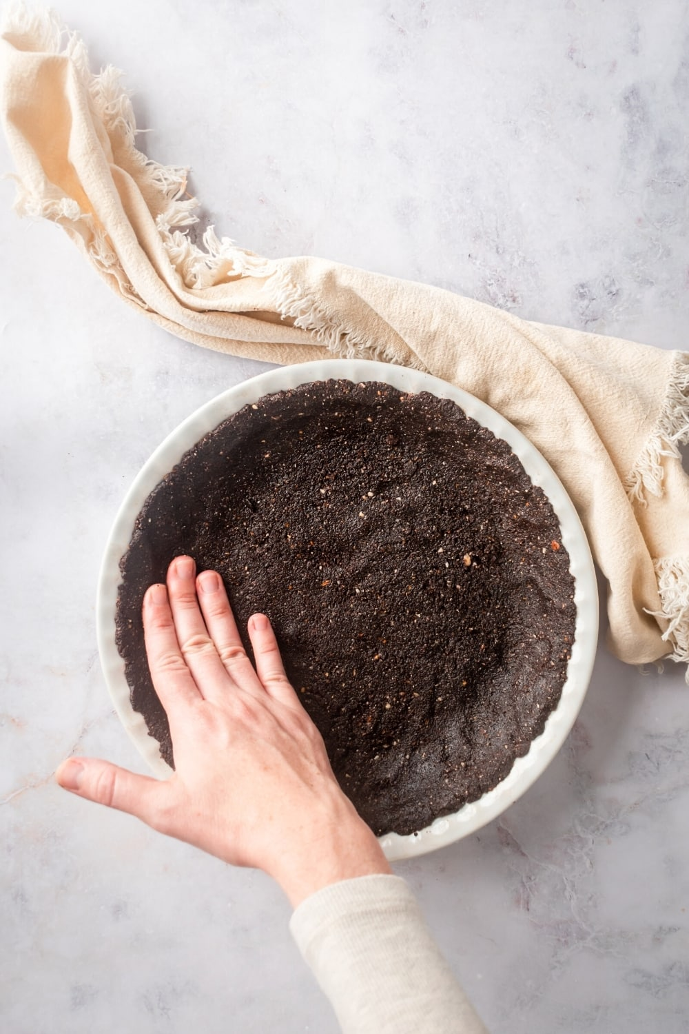 A white pie dish with a chocolate almond flour pie crust formed in it. There is a hand pushing the left side of the piecrust against the dish.