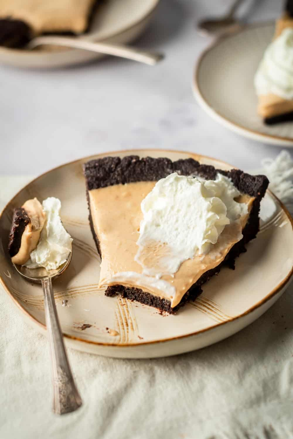 A slice of peanut butter chocolate pie on a white plate. A slice from the front of the pie is on a spoon that is to the left of the pie on the plate.